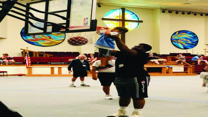 A volunteer helping a child 'dunk' at Basketball Camp.